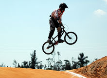 BMX Biker. A biker jumping a hill on a race track stock photography