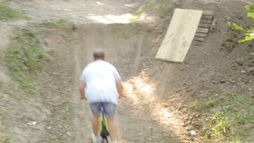 Bmx biker riding in forest stock video