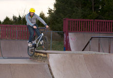 Bmx box grind. Teen Age BMX rider doing a grind at a skate park royalty free stock photo