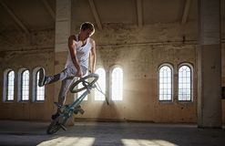 BMX-Bremsung und Sprungsreiten in einer Halle mit Sonnenlicht Stockfotografie