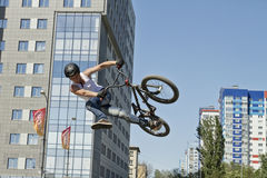 BMX cyclist performs a stunt jump. VOLGOGRAD - MAY 24: The BMX cyclist performs a stunt jump. The fifth annual competition for the Cup of Europe city Mall . May Royalty Free Stock Photography