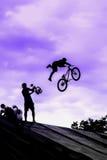 BMX-cykelbanhoppning i himmel på hög hastighet, svart kontur mot ljus himmel Extrem sport och risk Arkivbilder