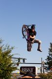 BMX Freestyle Vert Stunt. BMX freestyle stunt rider performs airborne jump trick, grabbing the seat with one hand; the other remains on the handlebar, body Royalty Free Stock Images
