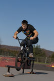 Bmx Grind. A teenage Bmx rider, does a rail slide at the skate park stock photos