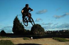 BMX Jump. BMX rider jumping over child Stock Photography