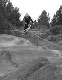 BMX rider catching air. A BMX rider catches some air jumping over a dirt berm Stock Photos