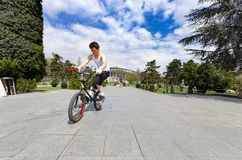 BMX Rider Cycling and Jumping in Park Outdoors, Stunt. Skopje, Macedonia - circa Apr, 2013: BMX Rider Cycling and Jumping in Park Outdoors, Stunt, Cycling Royalty Free Stock Image