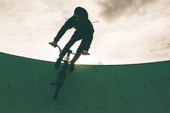 BMX rider doing tricks. Urban extreme sports. Concept royalty free stock image