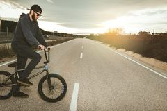 BMX rider doing tricks. Young man with a bmx bike. Extreme sports. Young man with a bmx bike. BMX rider doing tricks. Extreme urban sports concept royalty free stock images