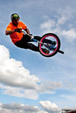 BMX Rider Gets Airborne Performing At State Fair. Hampton, GA, USA - September 27, 2014:  A young man with the High Roller BMX club rotates his bike in midair Royalty Free Stock Photos