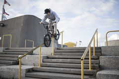 Bmx rider grinding on handrail Stock Images