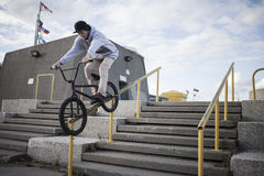 Bmx rider grinding on handrail Royalty Free Stock Photos