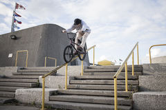 Bmx rider grinding on handrail Royalty Free Stock Photo