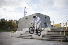 Bmx rider grinding on handrail royalty free stock images