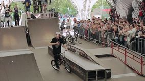 Bmx rider happy after perform in skate park. People apploud to him. Slow motion. stock video