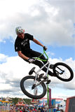BMX Rider Performs Midair Stunt At Georgia State Fair. Hampton, GA, USA - September 27, 2014:  A young man with the High Roller BMX club spins his bike in midair Stock Image