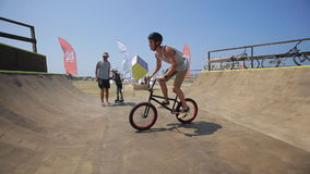 Bmx Rider rides a bike and practicing tricks in the BMX-Park stock video