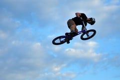 BMX-ryttare som gör en cykel att hoppa Arkivfoton