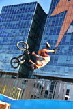 BMX sport jumping at a city background. Biking as extreme and fun sport. Stock Photos