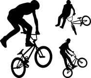 Bmx stunt cyclists silhouettes Stock Images