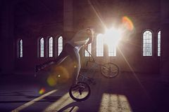 BMX stunt and jump riding in a hall with sunlight. Stock Images