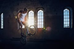 BMX stunt and jump riding in a hall with sunlight. Royalty Free Stock Photos