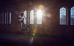 BMX stunt and jump riding in a hall with sunlight. BMX stunt and jump riding in a sunlight, indoor park royalty free stock photography