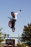 BMX stunt vertical. BMX rider performs a vertical (vert) jump stunt. [A tuck no hander.] This was a jump during a BMX vertical exhibition at a festival. 27th Royalty Free Stock Images