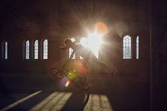 BMX stunts in a sunray indoor. BMX stunts in a sunray indoor gothic hall Stock Photography