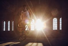 BMX stunts in a sunray indoor . BMX stunts in a sunray indoor gothic hall Royalty Free Stock Photos