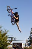 BMX Vertical Flying Stunt. BMX vertical (Vert) airborne exhibition, as an attraction at a festival. Man rides bike trough the air with one hand on seat Royalty Free Stock Photos