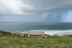 Bänkar på klippan nära havet med stormiga moln Royaltyfri Foto