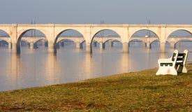 bänkbroar som förbiser parkfloden Royaltyfri Foto