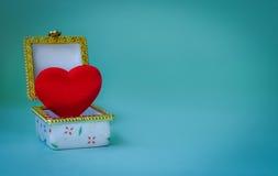 Boîte à bijoux avec un coeur à l'intérieur sur le fond bleu Photo stock