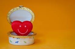 Boîte à bijoux avec un coeur souriant à l'intérieur sur le fond jaune Photographie stock libre de droits