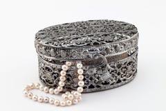 Boîte à bijoux découpée en métal d'isolement avec des perles sur le backgroun blanc Photographie stock libre de droits