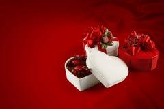 Boîte à chocolat de Saint-Valentin et de Noël (sur le fond rouge). Photo libre de droits