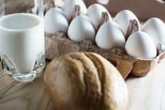 Boîte à oeufs ouverte de carton avec les oeufs blancs, le lait et le pain sur un fond en bois Image libre de droits