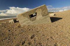 Boîte à pilules de la deuxième guerre mondiale descendant dans la plage pebbled, banque de Chesil Images libres de droits
