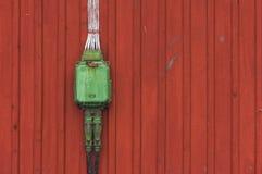 Boîte électrique sur un fond rouge en bois, poweroutlet en vert Photo stock