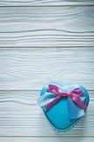 Boîte actuelle bleue en forme de coeur avec le ruban rose sur le panneau en bois cel Image stock