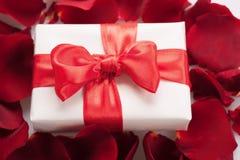 Boîte actuelle dans des pétales de rose Photographie stock libre de droits