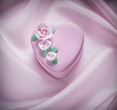 Boîte actuelle en forme de coeur sur des célébrations roses de fond de tissu Images stock