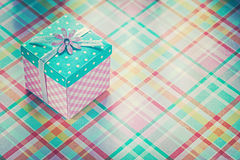 Boîte actuelle enveloppée sur le concep vérifié de vacances de fond de tissu Photographie stock