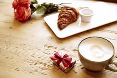 Boîte actuelle, fleurs roses, croissant frais, café sur la table en bois Le petit déjeuner romantique pour le jour du ` s de Vale Photo libre de droits