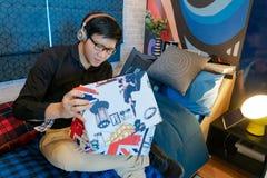 Boîte asiatique d'ouverture d'homme se reposant dans la chambre à coucher images stock