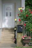 Boîte aux lettres et fleurs devant une maison Photo libre de droits
