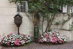 Boîte aux lettres et fleurs devant une maison dans le village médiéval d'en Auge de Beuvron dans des Frances de la Normandie Image stock