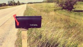 Boîte aux lettres isolée sur la route Photo stock
