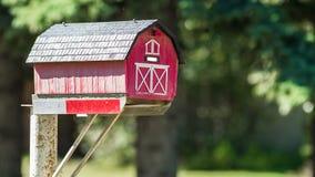 Boîte aux lettres rouge de grange un jour ensoleillé Photographie stock libre de droits
